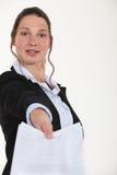 Woman handing over paperwork. Woman handing over completed paperwork Stock Images