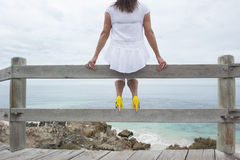 Woman on handrail at beach overlooking ocean Stock Photo