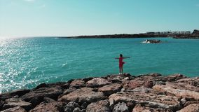 Woman with hands apart in air in red cute dress with wind flapping standing on rocky cliff looking at sun road and blue sea water. Aerial view of lady in red stock footage