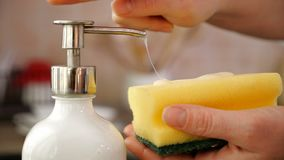 Woman hands apply washing up liquid from dispenser on sponge stock video footage
