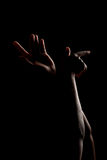 Woman hands arms. Hands and arms of a girl in low key on a black background Royalty Free Stock Images
