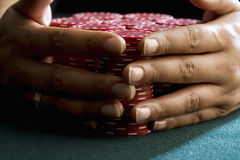 Woman with hands around piles of gambling chips on table, close-up of hands Stock Image