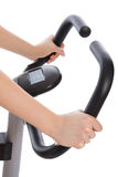 Woman hands on a bar stationary bike Royalty Free Stock Image