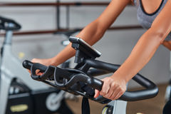 Woman hands on a bar stationary bike  the gym Royalty Free Stock Photos
