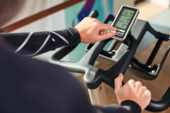 Woman hands on a bar stationary bike  the gym Royalty Free Stock Images