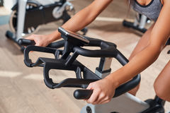 Woman hands on a bar stationary bike  the gym Stock Image