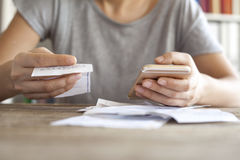 Woman hands with bills and mobile phone Stock Photos