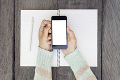 Woman hands with blank cell phone and diary. Mock up stock images