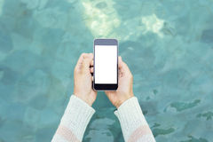 Woman hands with blank cell phone on a water surface background,. Mock up stock image