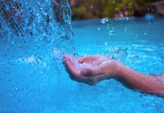 Woman hands and blue water. Fresh clean water current. Girl`s hands in water flow. royalty free stock image