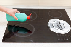 Woman hands with bottle of cleaning detergent for induction stove applies a scour to the burner.  Stock Image