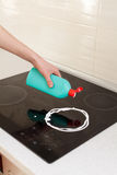 Woman hands with bottle of cleaning detergent for induction stove applies a scour to the burner. House cleaning. Woman hands with bottle of cleaning detergent Stock Photos