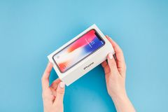 Woman hands with the box of Apple iPhone X. BERLIN, GERMANY - MAY 24, 2018: Woman hands holding the colorful box of the latest Apple iPhone X 10 smartphone royalty free stock image