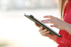 Woman hands browsing a tablet outdoors. Profile of a woman hands browsing a tablet and touching screen with finger outdoors Royalty Free Stock Images