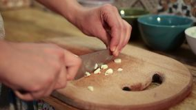 Woman hands chopping fresh garlic with knife stock video footage