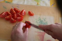 Cutting tomatoes slice on cutting board, woman hands close up from above Stock Images