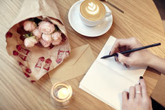 Woman hands close-up writing at notebook or postcard, blank layout for design. Flowers and coffee in cafe on wooden table, St. Val