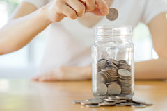Woman hands with coins in glass jar, Royalty Free Stock Photos