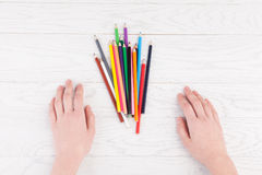Woman hands and Colour Pencils on table Stock Image