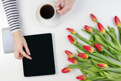 Woman hands with computer tablet, cup of coffee, mobile phone and beautiful flowers bunch on the white office table Stock Photos
