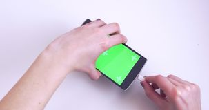 Woman Hands Connecting Cable To Smartphone With Green Chroma Key Screen On White Background. 4K Cinema stock footage