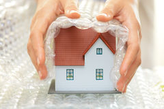 Woman hands covering a model house with bubble wrap- house protection or insurance concept stock photo