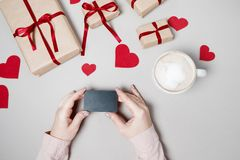 Woman hands with Credit card, gift box with heart and coffee on. White background. Valentine day, online shopping concept, holiday background. Top view Royalty Free Stock Photography