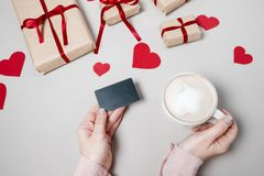 Woman hands with Credit card, gift box with heart and coffee on. White background. Valentine day, online shopping concept, holiday background. Top view Stock Photography