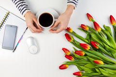 Woman hands with cup of coffee and computer mouse. Mobile phone, paper notebook and beautiful tulips on white table Royalty Free Stock Photo