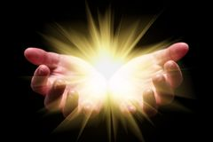 Woman hands cupped holding, showing, or emanating bright, glowing, radiant, shining light. Emitting rays or beams expanding. Religion, divine, heavenly stock image