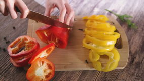 Woman hands cuts pepper on a wooden table stock video
