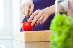 Woman hands cuts a tomato Royalty Free Stock Image