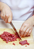 Woman hands cutting beef Stock Images