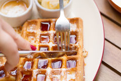 Woman hands cutting belgium waffles with fork and knife on plate with butter, maple sauce on wooden table Stock Photo
