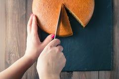 Woman hands cutting manna pie Royalty Free Stock Photos