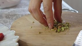 Woman hands cutting pistachios on wooden cutting board. Woman hands cutting pistachios with big knife on wooden cutting board filmed from eye level in slow stock video footage