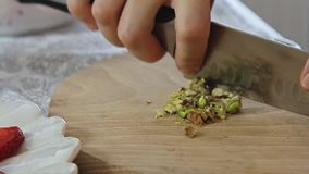 Woman hands cutting pistachios on wooden cutting board. Woman hands cutting pistachios with big knife on wooden cutting board filmed from eye level in slow stock footage