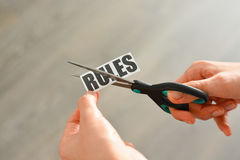 Woman hands cutting with scissors a printout reading 'RULES'. Woman hands cutting with scissors a printout of the word 'rules stock photo
