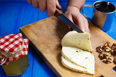 Woman hands cutting spicy homemade cheese on cutting board, serv. Healthy food, home cooking, cheese slices. Woman hands cutting spicy homemade cheese on cutting Royalty Free Stock Photography