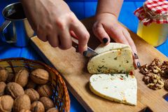 Woman hands cutting spicy homemade cheese on cutting board, serv. Healthy food, home cooking, cheese slices. Woman hands cutting spicy homemade cheese on cutting Stock Photography