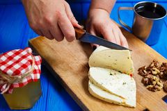 Woman hands cutting spicy homemade cheese on cutting board, serv. Healthy food, home cooking, cheese slices. Woman hands cutting spicy homemade cheese on cutting Stock Photos