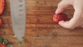 Woman hands cutting strawberries on wooden cutting board stock footage