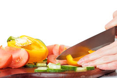 Woman hands cutting vegetables for a salad on a cutting board. Pepper, cucumber, tomato. Stock Photography