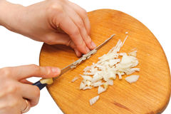 Woman hands cutting white onion on a kitchen board. Cooking food Stock Photo