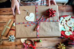 Woman hands delivering a Christmas gift. Royalty Free Stock Image