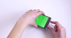 Woman Hands Disconnecting Cable To Smartphone. With Green Chroma Key Screen On White Background stock footage
