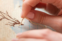 Woman hands doing cross-stitch. Royalty Free Stock Image
