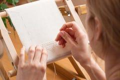 Woman hands doing cross-stitch. Stock Photos
