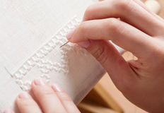 Woman hands doing cross-stitch. Royalty Free Stock Photo