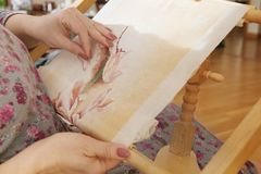 Woman hands doing cross-stitch embroidery on a linen cloth on an embroidery machine.  Stock Images